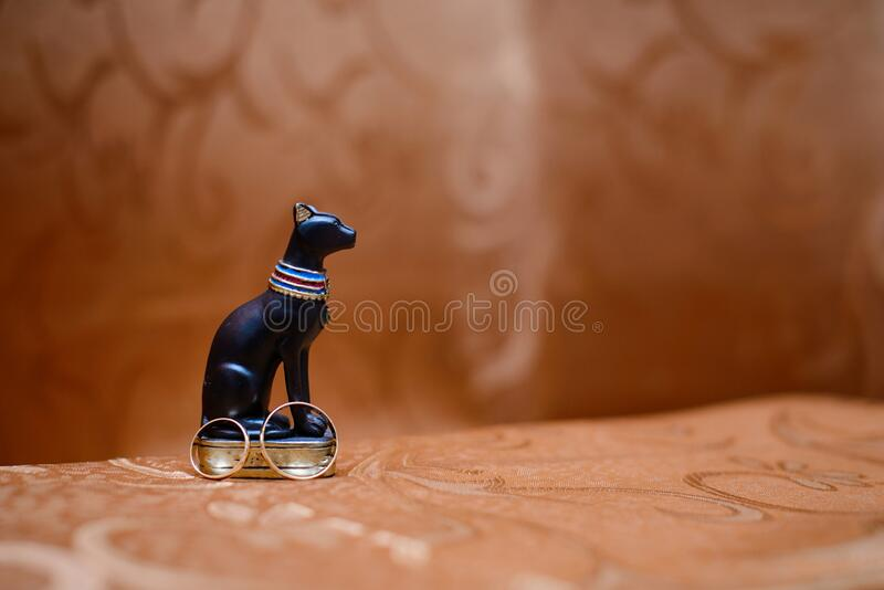 Gold wedding rings next to a statuette of an Egyptian black cat on a brown background.  royalty free stock photo