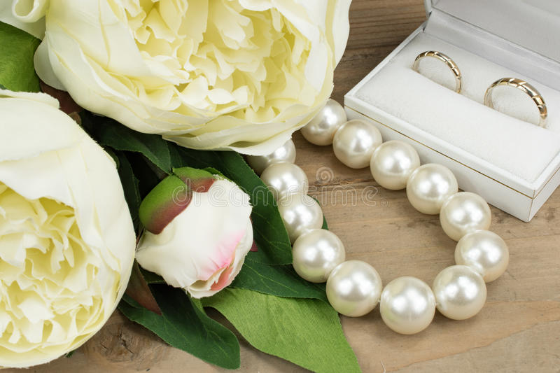 Gold Wedding Rings, Pearl necklace and Peony flowers. Close-up. Wedding concept: Close up of pair gold wedding rings, white pearl necklace and creme peony roses royalty free stock photos