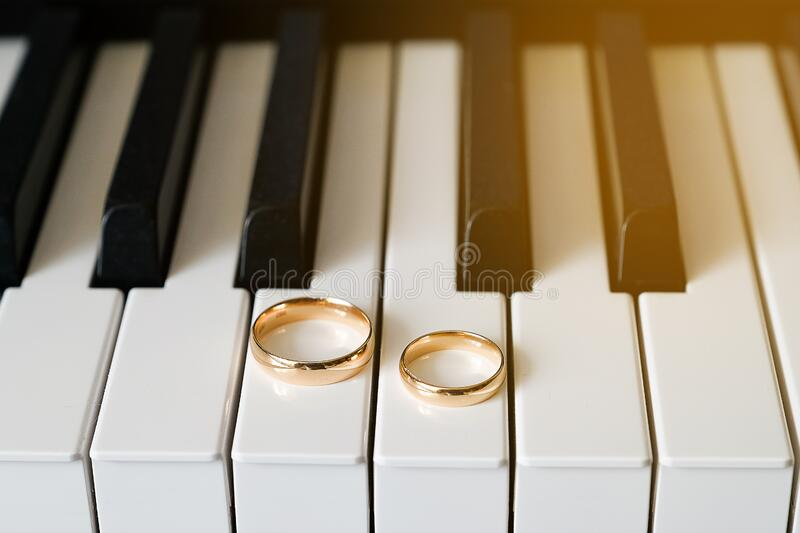 Gold wedding rings on the piano keyboard. Tinted Photo.  royalty free stock image