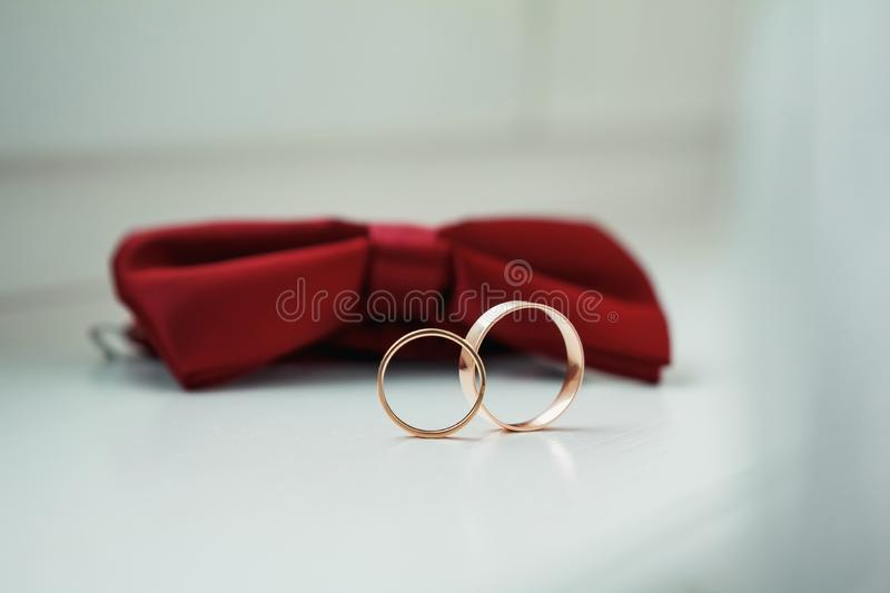 Gold wedding rings on a red butterfly on a windowsill royalty free stock photos