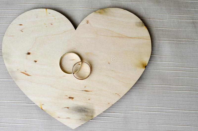 Gold wedding rings on a wooden heart. Bright, glittering, glamorous, fashionable, expensive hearts made of wood with adornments fo stock images