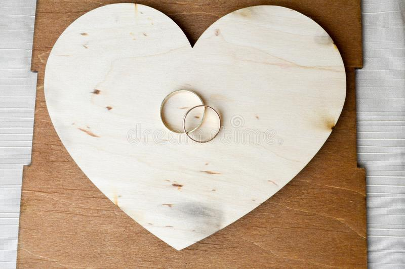 Gold wedding rings on a wooden heart. Bright, glittering, glamorous, fashionable, expensive hearts made of wood with ornaments for. St. Valentine`s Day on a stock images