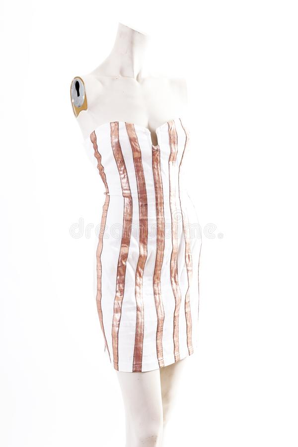 Gold white mini dress cocktail wear on mannequin full body shop display. Woman fashion styles, clothes on white studio background.  royalty free stock image