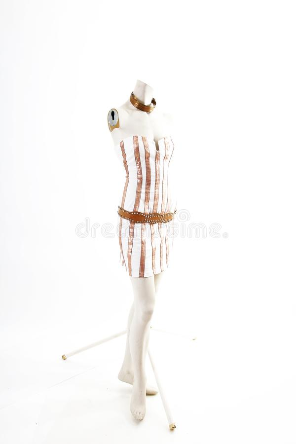 Gold white mini dress cocktail wear on mannequin full body shop display. Woman fashion styles, clothes on white studio background. stock photography