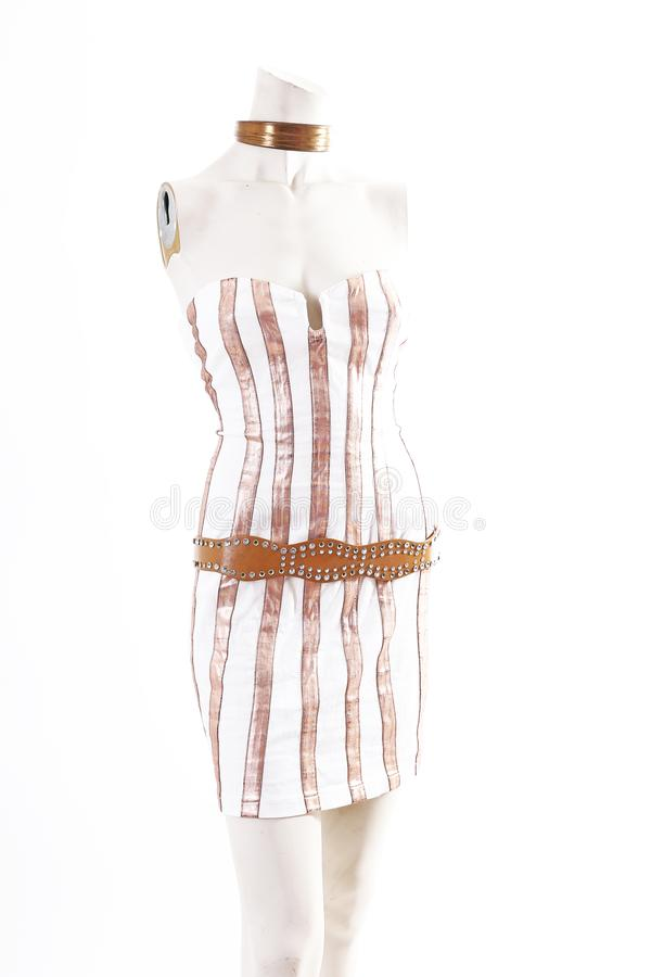 Gold white mini dress cocktail wear on mannequin full body shop display. Woman fashion styles, clothes on white studio stock photo