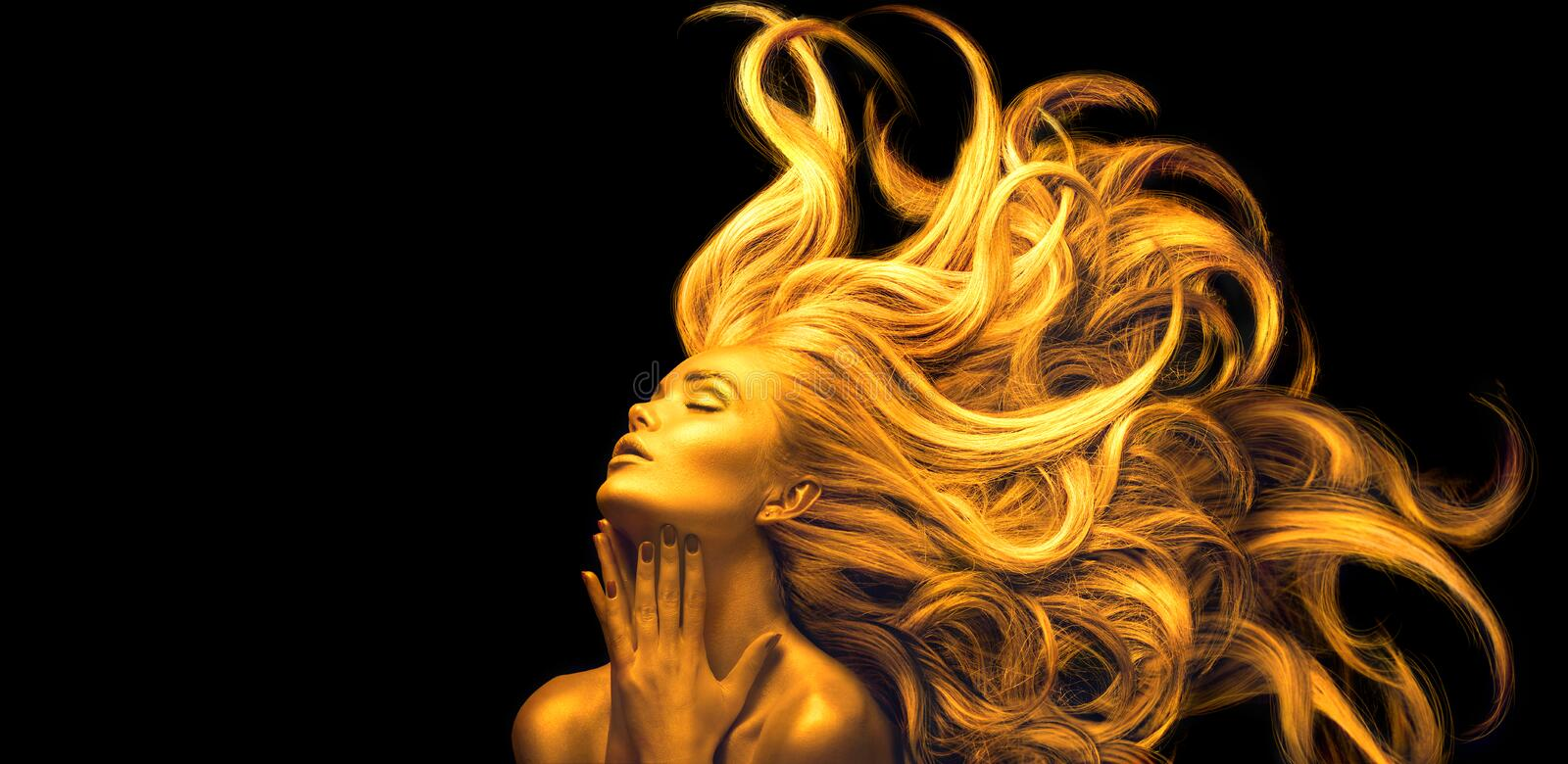 Gold Woman. Beauty fashion model girl with Golden make up, Long hair on black background. Gold glowing skin and fluttering hair. Metallic, glance Fashion art stock images
