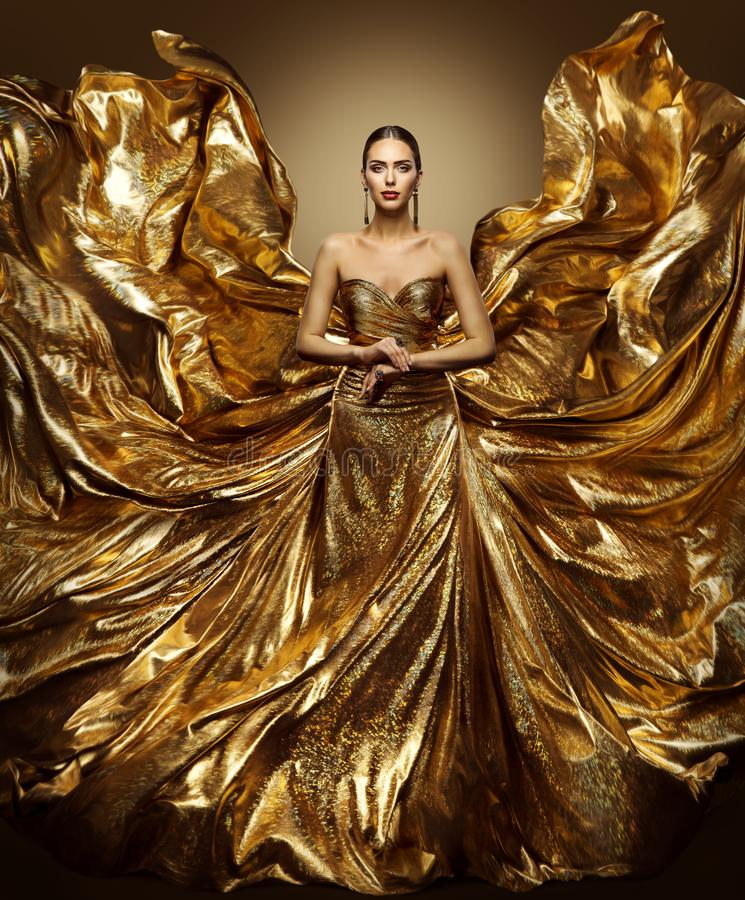 Gold woman flying dress, fashion model in waving art golden gown royalty free stock photos