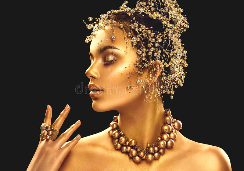 Gold woman skin. Beauty fashion model girl with golden makeup royalty free stock photography