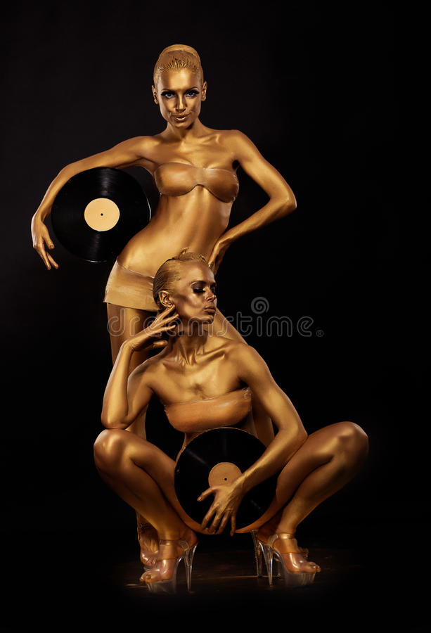 Gold Bodyart. Coloring. Golden Women Silhouettes with Retro Vinyl Records over black. Creative Art Concept. Gold Women Silhouettes with Retro Vinyl Records royalty free stock photography