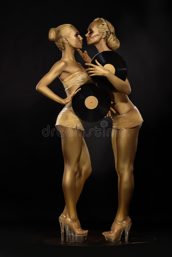 Futurism. Creativity. Glossy Golden Women with Vinyl Record over Black. Shiny Gilded Bodyart stock images