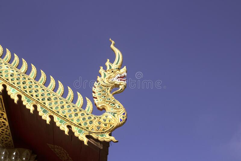 Gold wooden dragon head on Thai traditional eaves roof at temple in Thailand.  stock image