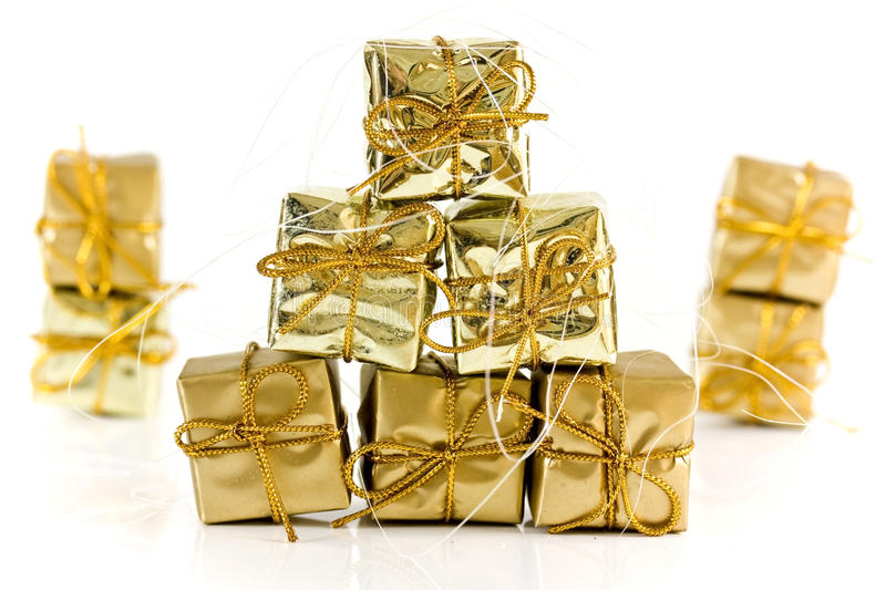 Gold wrapped parcels on white stock photos