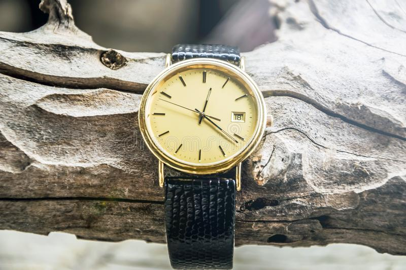 Gold wrist watch with leather strap on wooden background. Clock, time, watch, old, antique, isolated, hour, white, vintage, minute, retro, pocket, alarm, gold royalty free stock image