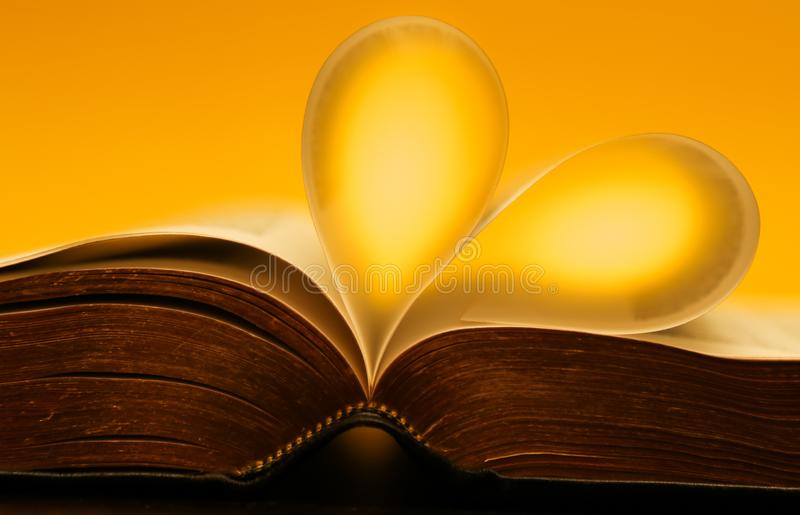 Gold, yellow glowing pages of a bible forming a heart royalty free stock image