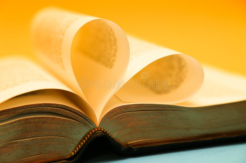 Gold, yellow glowing pages of a bible forming a heart royalty free stock photography