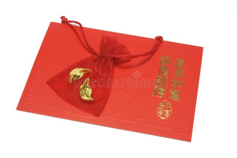 Goldbarren im Quetschkissen auf chinesischer Gruß-Karte stockbilder