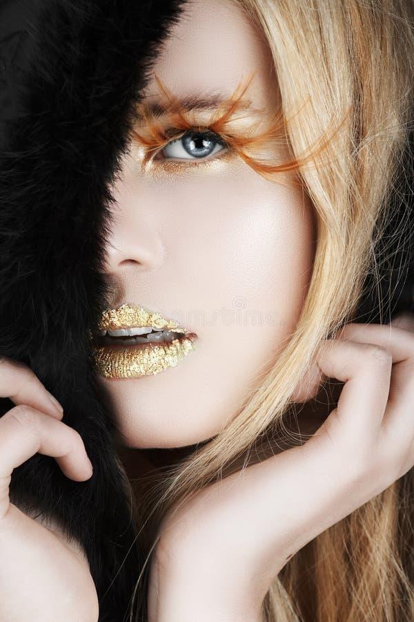 Goldblatt und falsche Wimpern auf einer blonden Frau lizenzfreies stockbild