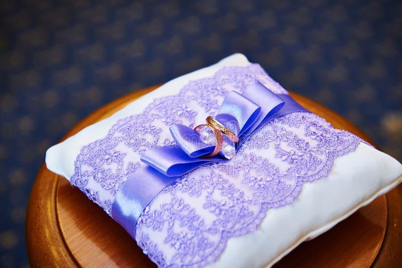 Goldehering auf einem schönen weißen Kissen lizenzfreie stockbilder