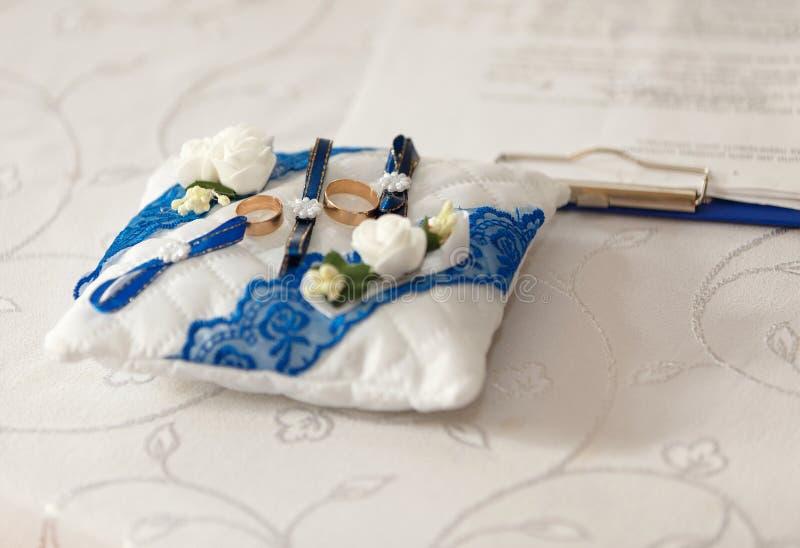 Goldeheringe auf einem weißen blauen Kissen stockfoto