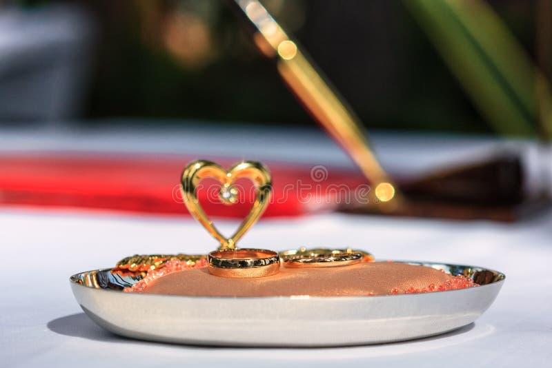 Goldeheringe auf künstlichem Kaviar verzierten Auflage mit einem Herzen auf weißem Gewebe- und Stifthintergrund Heiratregister am lizenzfreie stockfotos