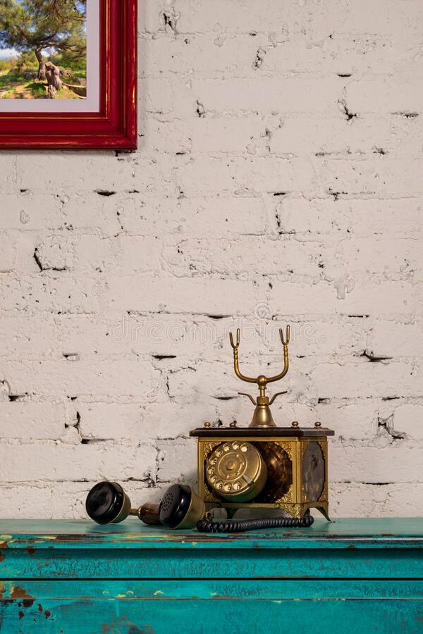 Golden antique telephone set on top of green vintage wooden table and background of white bricks wall royalty free stock photos