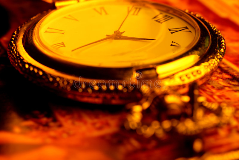 Golden antique watch. In golden background stock image