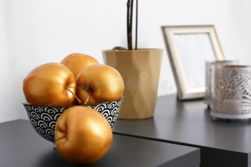 Golden apples on dark table in room royalty free stock image