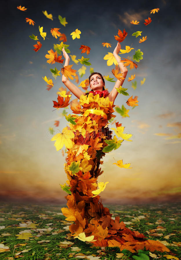 Golden Autumn. Beautiful lady Autumn in the dress from yellow maple leaves royalty free stock photography