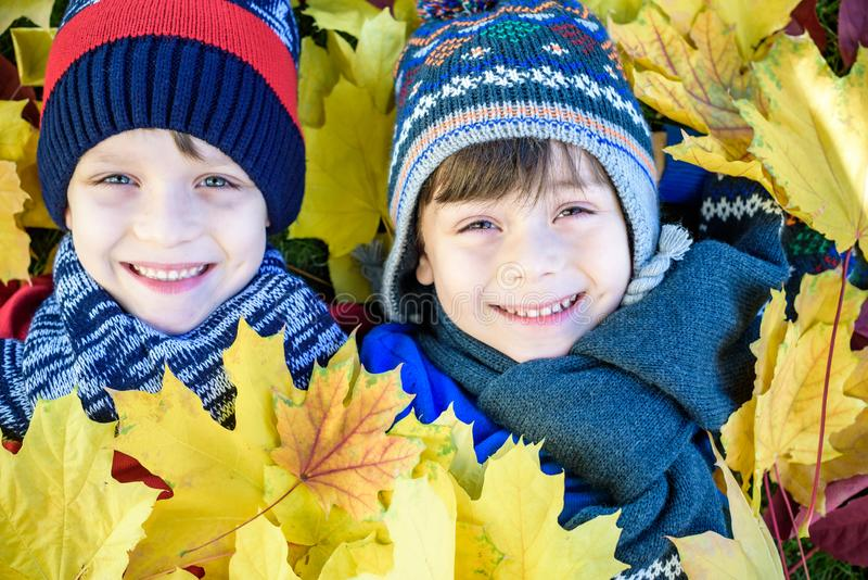 Golden Autumn, group of children lie on their backs in yellow leaves, Happy children in autumn park lying on leaves royalty free stock photos