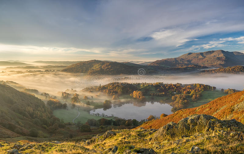 Golden Autumn sunrise in a valley of the Lake District. An autumn sunrise looking over the foggy Langdale Valley in the Lake District, with strong autumn colours stock photo