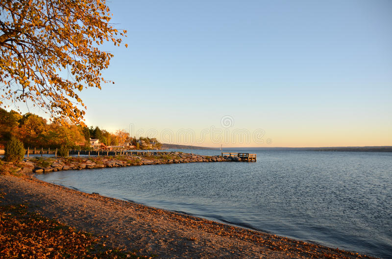 Golden Autumn sunset on Cayuga Lake shoreline. Calm, blue evening waters of Cayuga Lake shoreline cove, with warm golden colors of summer sunset stock image