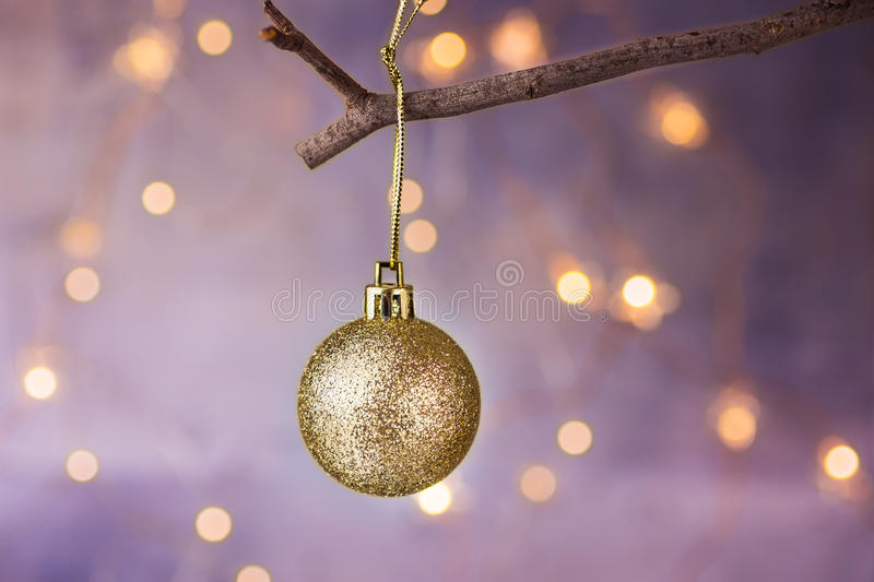 Golden ball Christmas ornament hanging on dry tree branch. Shining garland golden lights. Beautiful pastel background stock photo