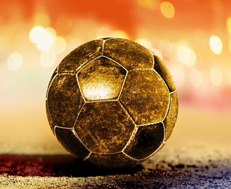 Golden ball on ground. Golden soccer ball on ground of football field stock images