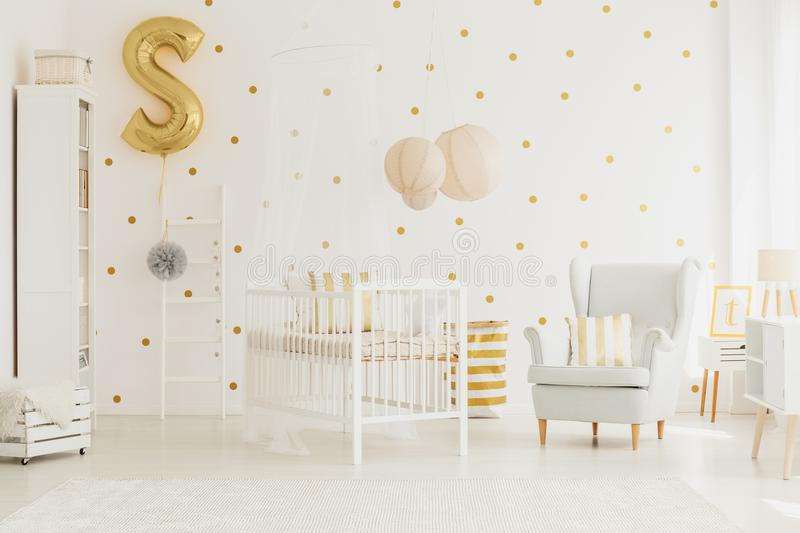 Golden balloon pinned to ladder. Letter shaped golden balloon pinned to white wooden ladder with tulle pompom in baby bedroom with wall with dots stock images