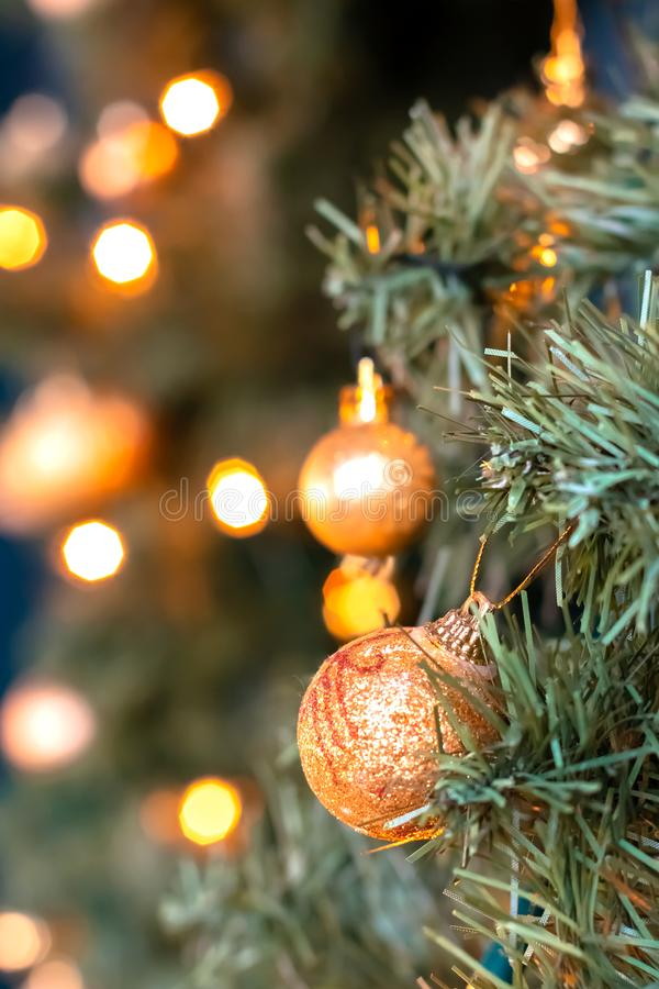 Golden balls and bokeh lights on a green Christmas tree, winter background for greeting card, atmosphere of cosiness and. Celebration royalty free stock photos