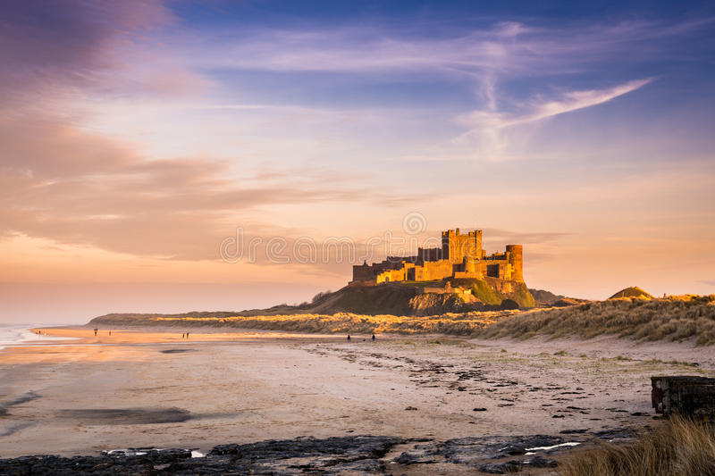 Golden Bamburgh Castle. Bamburgh Castle on the Northumberland coastline, bathed in late afternoon golden sunlight royalty free stock photography