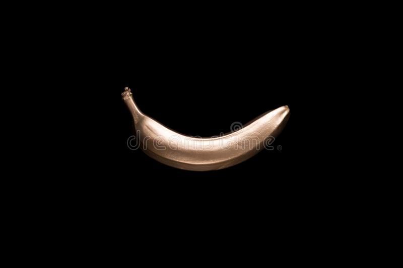 Golden banana on a black background. Creative concept with fruit. stock images