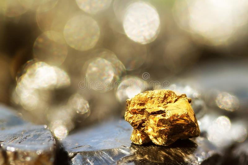 Golden bar on raw coal nuggets with soft focus and shiny background.  stock image