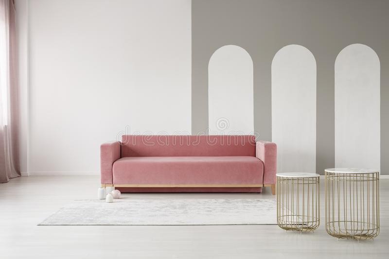 Golden basket tables and a pink sofa in an elegant living room interior with gray arches on a white wall. Golden basket tables and a pink velvet sofa in an stock images