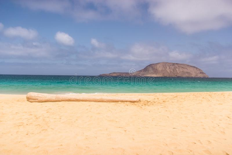 Golden beach with a trunk, blue ocean with little island in background on a cloudy day, La Graciosa, Cary Island royalty free stock photography