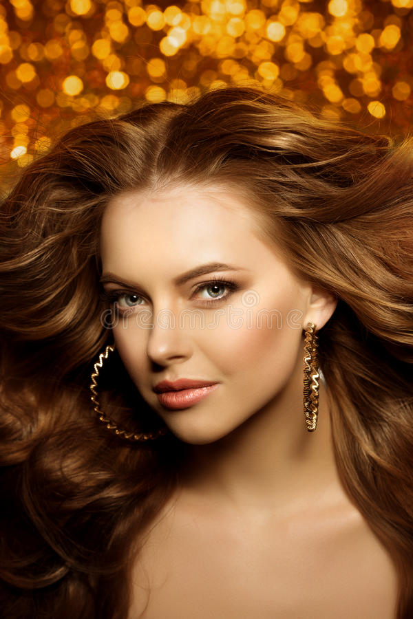 Golden beautiful fashion woman, model with shiny healthy long v royalty free stock photography