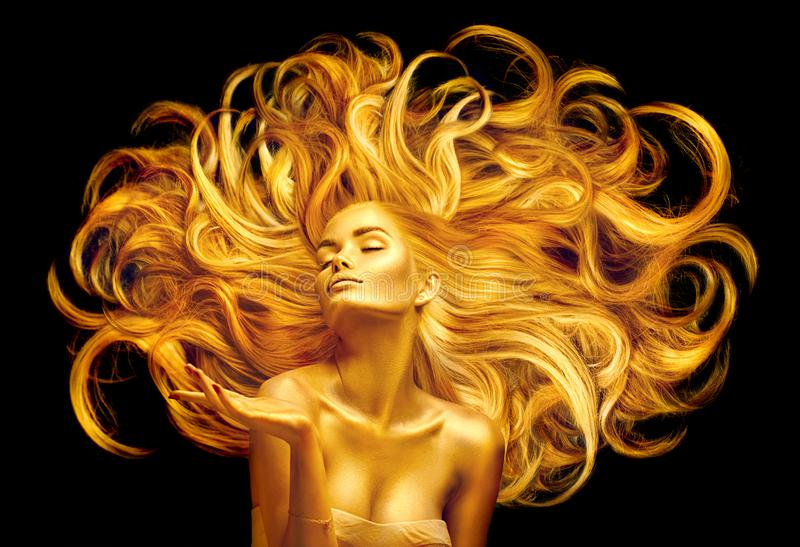 Golden beauty woman. Sexy model girl with golden makeup and long hair pointing hand over black. Metallic gold glowing skin. And fluttering hair stock photography