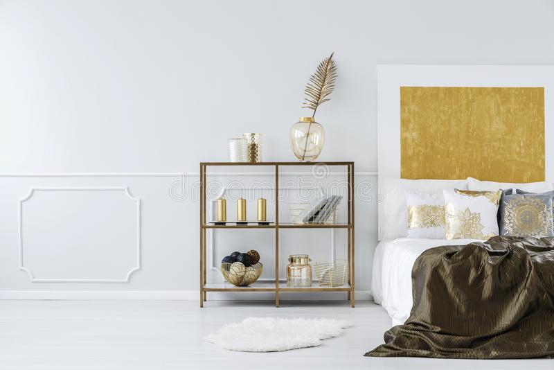 Golden bedroom interior. With bed, metal shelf and wall molding stock images