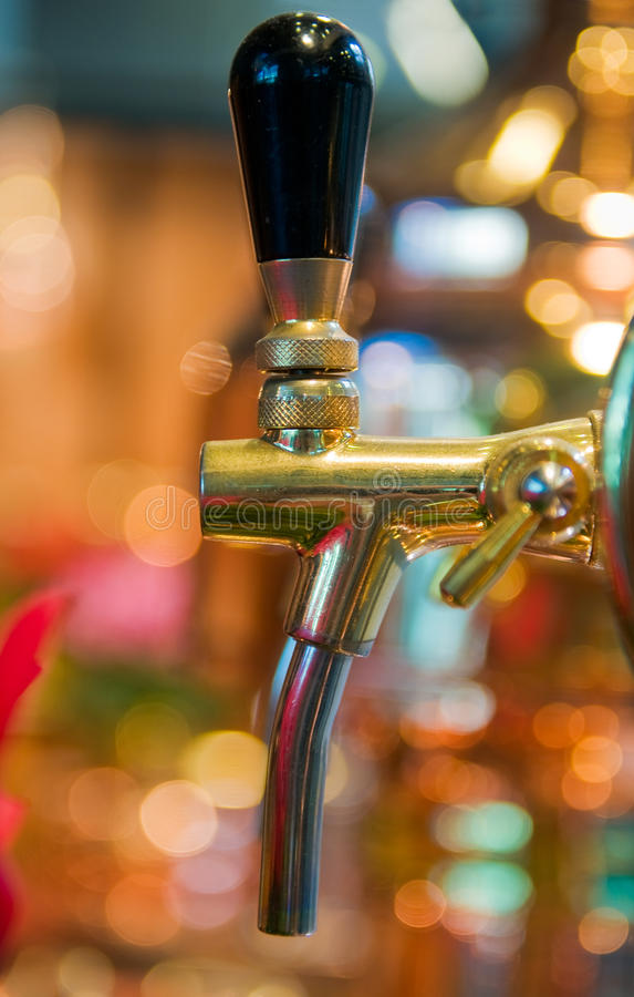 Golden beer tap. Close up of golden beer tap with blurred background stock photos
