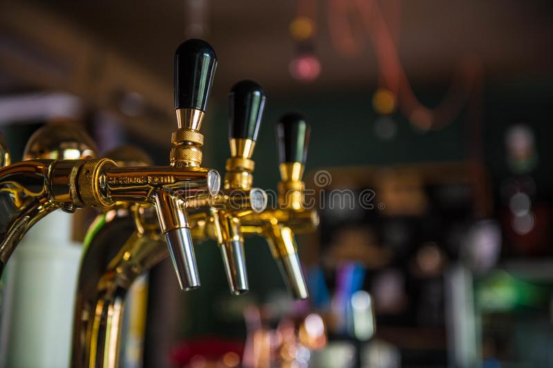 Golden beer tap with blurred background.  stock photos