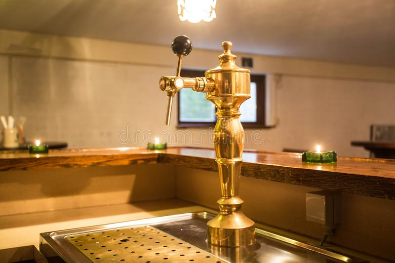 Golden beer tap in empty bar. With candle light royalty free stock photos