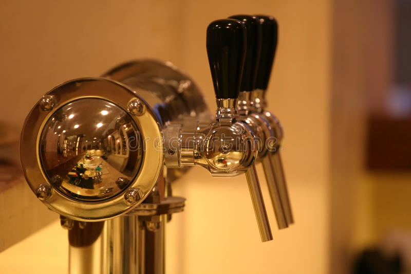 Golden beer tap. In the pub stock photography
