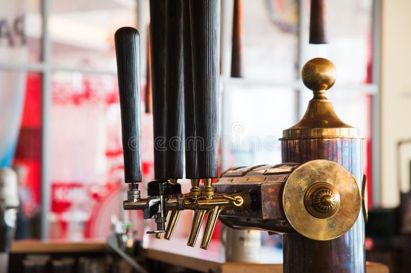 Golden beer tap. Golden shiny beer taps in beer bar stock photos