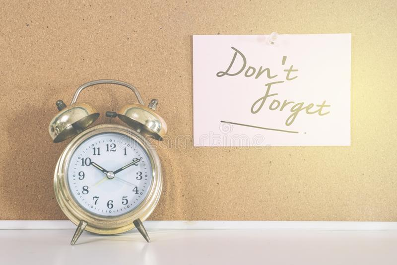 Golden bell alarm clock and a note writen DON`T FORGET on a cork board stock image