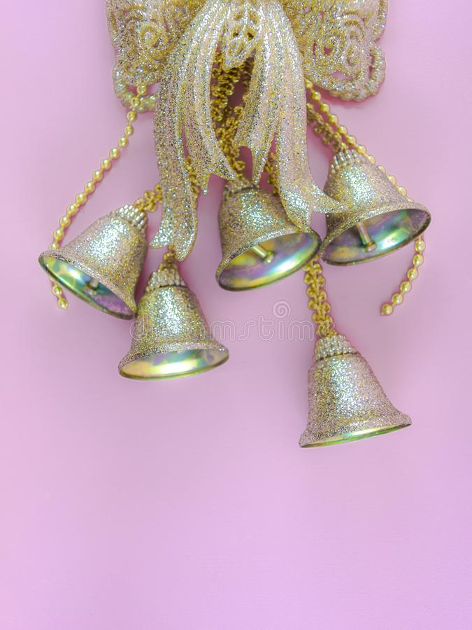 Golden bells christmas ornament in pink background. Decoration, december, xmas, color, sparkling, shiny royalty free stock photography